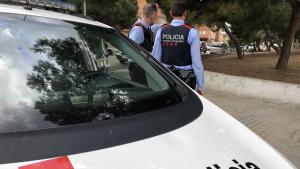 Dos agents dels Mossos amb un vehicle policial