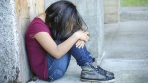 Imatge d'arxiu d'una nena asseguda a terra.