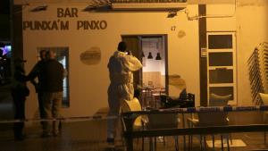Imatge de la façana del bar Punxa'm Pinxo de Sant Carles de la Ràpita amb un agent de la policia científica dels Mossos