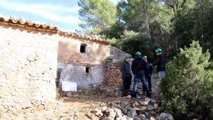 Imatge d'una de les façanes del Mas de Burot als Ports d'Horta de Sant Joan, amb un grup d'arquitectes, tècnics i l'alcalde Joaquim Ferràs