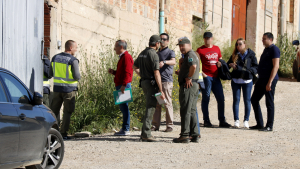 Pla mitjà on es poden veure agents de la policia espanyola amb Agents Rurals a la porta d'accés del magatzem de Bell-lloc d'Urgell