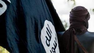 Un militante de Estado Islámico exhibe su bandera en Raqa.