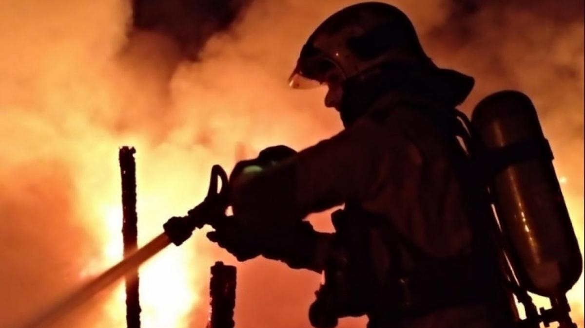 Un bomber apagant l'incendi declarat ahir a la nit a Sabadell