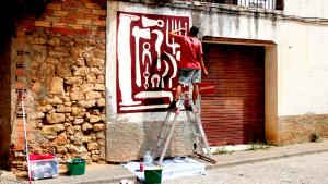 Un artista treballant en una de les creacions del festival Riu d'Art de Riba-roja d'Ebre