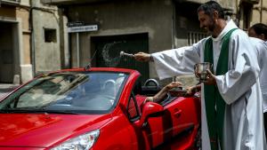 El mossèn Àguila beneeix un vehicle a Valls durant la celebració de Sant Cristòfol, patró dels conductors.