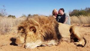 Fotografía de la pareja haciéndose el beso detrás del león