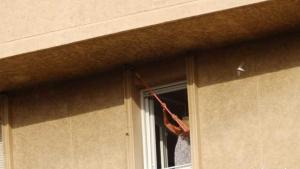 Imatge de la dona destrossant nius d'oreneta cuablanca, en un bloc de pisos de Barcelona