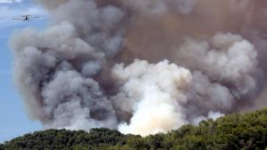 Un hidroavió combat una espessa columna de fum en l'incendi de 2016 a la Pobla de Montornès.