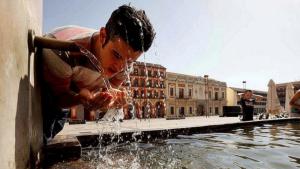 Un jove es refresca en una font sota un sol de justícia i temperatures extremes