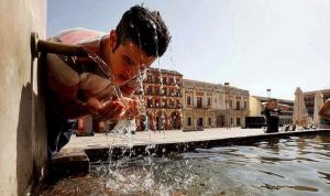 Un joven se refresca en una fuente bajo un sol de justicia y temperaturas extremas