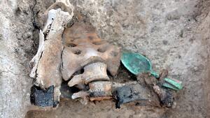 Detall de l'abdomen d'un cadàver enterrat amb el cinturó i una cullera