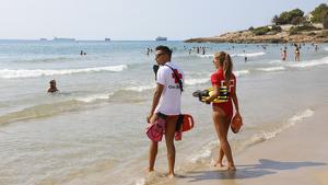 Dos socorristes de la Creu Roja, de costat, mirant cap al mar a la platja de l'Arrabassada de Tarragona.