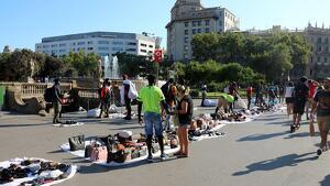 Els manters han estat fent i desfent els farcells amb productes a la plaça de Catalunya aquest dissabte