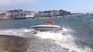 La mala mar envia una llanxa contra les roques de la sortida de la riera de Cadaqués