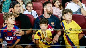 Leo Messi i Luis Suárez amb els seus fills mirant el partit