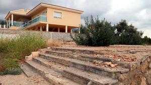 Primer pla de les escales que es van salvar de l'explosió i el solar cimentat que ha quedat on hi havia el xalet dels terroristes del 17-A