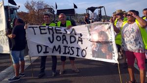Un grup de manifestants afectats pels focs del juny mostrant una pancarta que demana la dimissió de la consellera Teresa Jordà.