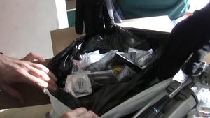 Unes mans dels agents policials obrint una bossa amb preservatius, en l'operació contra la pornografia infantil.