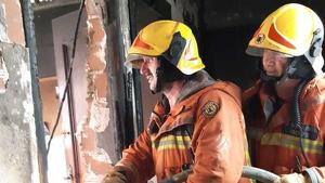 Els bombers en la casa a on s'ha iniciat l'incendi