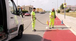 Operaris senyalitzant el nou tram de carril bici al carrer Mas de la Vileta.