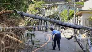 Un policía inspecciona el poste eléctrico caído
