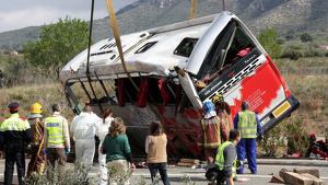 Efectius mirant com la grua està aixecant l'autobús accidentat a l'AP-7 a Freginals, el 20 de març del 2016