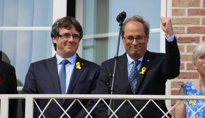 El president Quim Torra aixeca un puny al costat de Puigdemont, en un acte a Waterloo el 28 de juliol