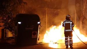 Els Bombers apagant el foc als contenidors que s'han cremat.