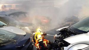 Els bombers treballen en l'incendi de la planta de desballestament de vehicles de Massamagrell