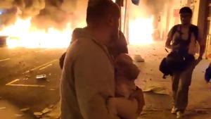 Imatge del pare fugint de les flames per protegir el menut