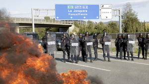 La Policia Nacional i una barricada cremant a l'AP-7 a Girona Oest