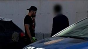 Omar Montes junto a dos coches de policía