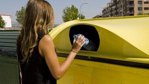 Una dona tirant una ampolla de plástic en un contenedor groc.