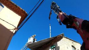 Els Bombers de la Generalitat retirant la teulada metàl·lica de Benissanet amb l'ajuda d'una grua de gran tonatge