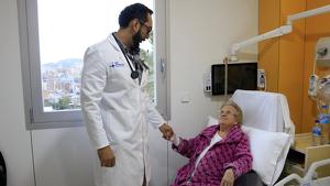 Eulalia, una pacient de 96 anys, s'agafa de la mà del doctor a l'habitació de la Unitat de Fragilitat conjunta de Vall d'Hebron i Sant Rafael