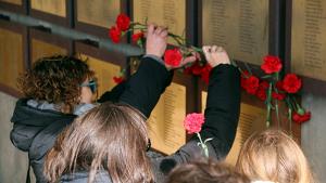 Familiars dipositant clavells rojos sota les plaques que recorden les víctimes de la Guerra Civil al memorial de les Camposines