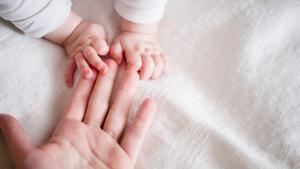 Imagen de archivo de un bebé cogiendo la mano de su madre