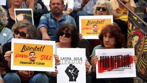 Imatge de diverses persones amb cartells que demanen la llibertat dels joves tarragonins empresonats durant els disturbis
