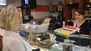 Imatge d'Encarna Clares, de la pastisseria Cabal, mostrant a una clienta una safata de panellets amb motius del procés
