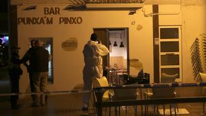 La façana del bar Punxa'm Pinxo de Sant Carles de la Ràpita amb un agent de la policia científica dels Mossos