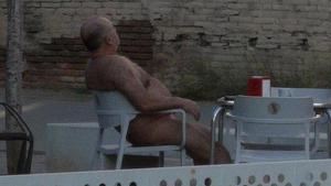 L'home despullat es va asseure en una terrassa del barri
