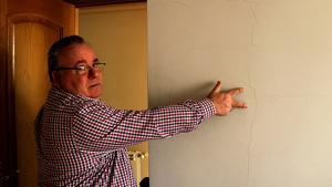 Monllaó mostrant una esquerda a la paret d'una habitació de la seva casa d'Amposta
