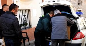 Pla mitjà on es poden veure agents de la Guàrdia Civil amb un dels detinguts a l'operació