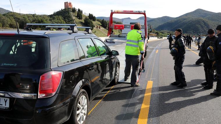 Una grua enduent-se un cotxe al tall de l'AP-7 a La Jonquera