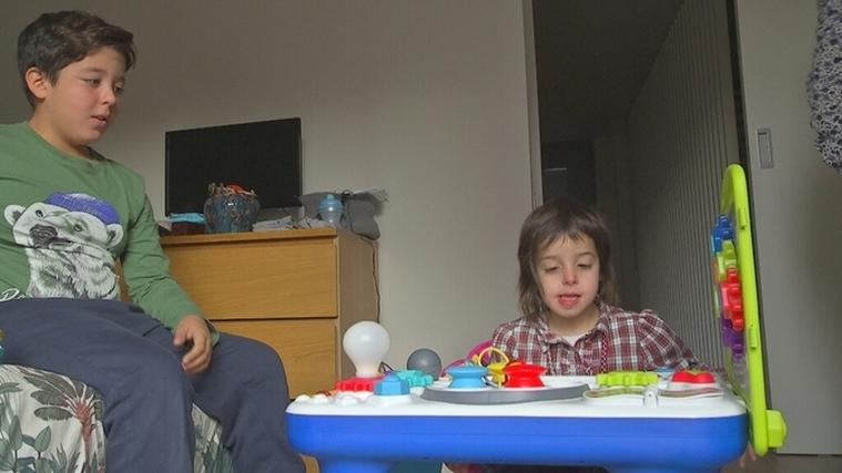 La Clàudia, una nena de sis anys amb una malaltia única al món, jugant amb el seu germà gran