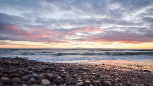 Imatge d'una platja i un cel mig tapat per núvols