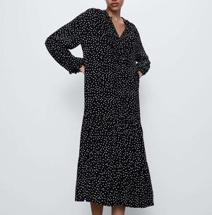 Modelo con un vestido 'midi' negro de estampado de lunares en blanco