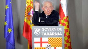 El actor Albert Boadella detrás de un atril y delante de unas banderas