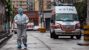Imagen de una ambulancia china y un especialista con traje y mascarilla