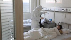 Un médico atiende a un paciente con fiebre en una sala de aislamiento en un hospital del condado de Yinan